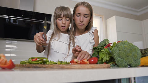 Two girls in white dresses are cutting vegetables at home in the kitchen. Two Footage