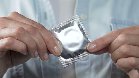 Female fingers holding sealed condom, sexually transmitted diseases, protection Footage
