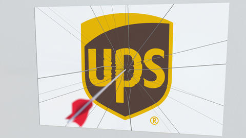 Archery arrow breaks glass plate with UPS company logo. Business issue Live Action