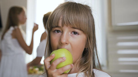 The girl is eating a big green apple. Close-up. A handsome teen is eating a Footage