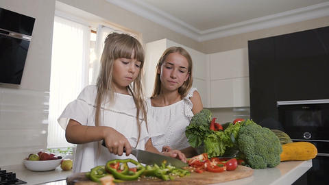 Two attractive sisters make vegetable slicing. Girls slices paprika and prepare Footage