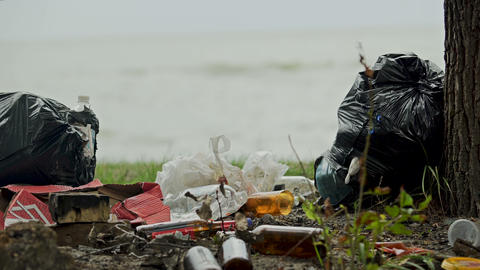 Huge plastic bags of rubbish on shore, people neglecting environmental dangers Live Action