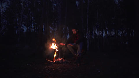 A young bearded guy sits in a chair and warms his hands by the fire. Forester by ビデオ