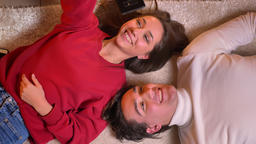 Top shot of young beautiful couple lying head to head on carpet and making Footage