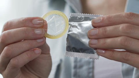 Girl fingers taking condom from package, prevention of HIV AIDS, contraception Footage