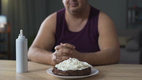 Corpulent man decorating chocolate cake with whipped cream, unhealthy food Live Action