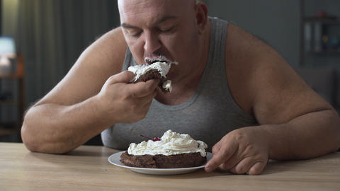 Obese person eating cake with whipped cream greedily and quickly, addiction Footage