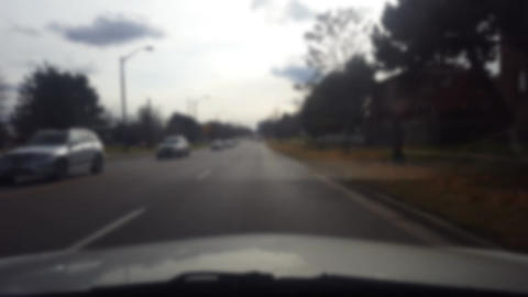 Driving Along a Suburban Road Ending at Intersection With Blur Effect. Unfocused Live Action