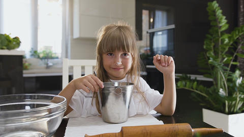 Small funny girl is cooking and mixing flour in the bowl. Portrait shot. Close Footage