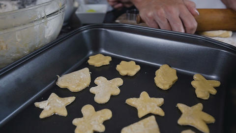 Raw shape cookies with sugar icing on baking tray. Woman is making the Live Action