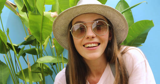 Attractive smiling young woman in eyeglasses near plants Footage