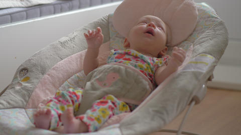 Baby of two months in rocking chair at home Live Action