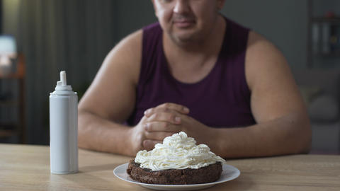 Fat male decorating cake with whipped cream and putting cherry on the top Footage