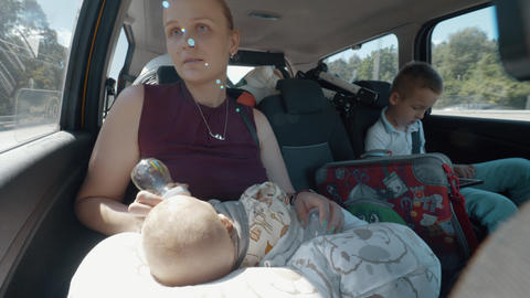 Family car journey. Mum traveling with children Live Action