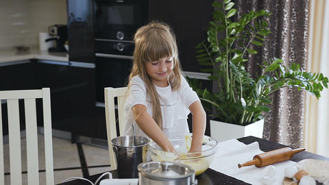 Smile little girl kneading a dough l in a big glass of bowl in the kitchen Footage