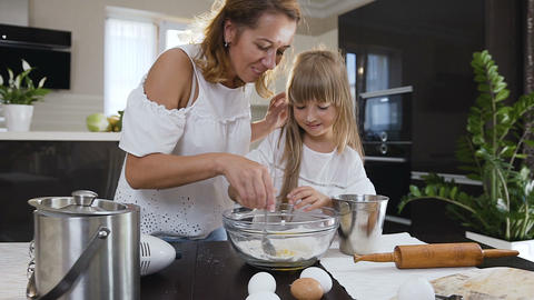 Little girl helping her mom in the kitchen by stirring the ingredients for their Footage