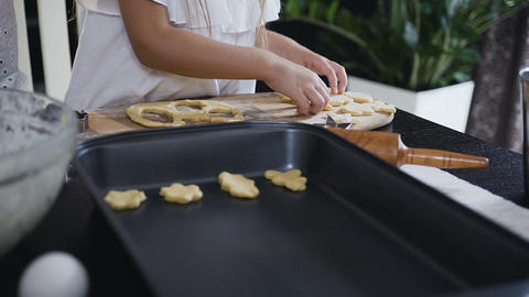 Small girl puts a raw cookie on baking tray. The child, together with his mother Live Action