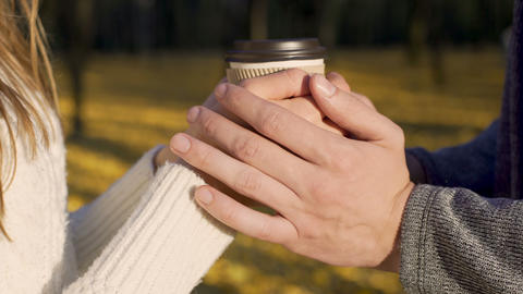 Lovers warming their frozen hands with cup of warm beverage, autumn date Footage