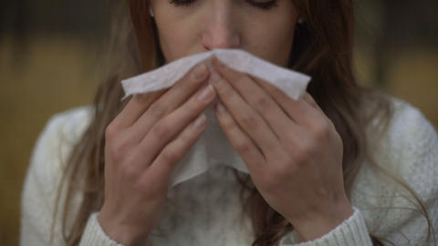 Girl suffering from runny nose and teardrop discharge, symptom of seasonal virus Live Action