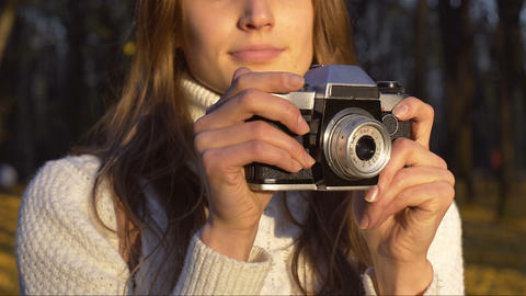 Talented girl taking pictures of beautiful autumn nature on old vintage camera Footage