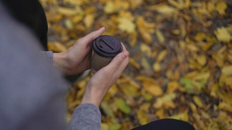 Lonely guy warming frozen hands with hot beverage, broken heart in cold autumn Live Action