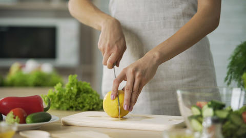 Female cutting lemon and squeezing fresh juice into salad, vegan, vegetables Footage