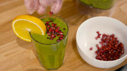 Man is Decorating Spinach Smoothie Cocktail with Orange and Pomegranate Footage