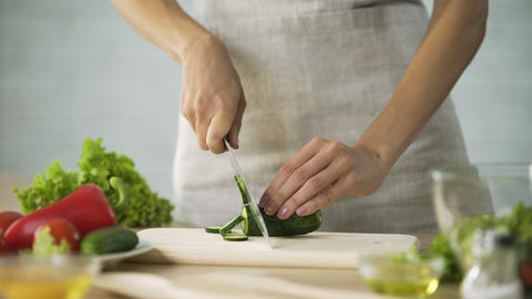Female chef slicing fresh cucumber with a knife on wooden board, vegetables Live Action