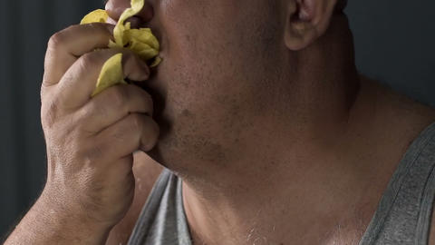 Man eating crisps with appetite, psychological problem, unhealthy food addiction Live Action