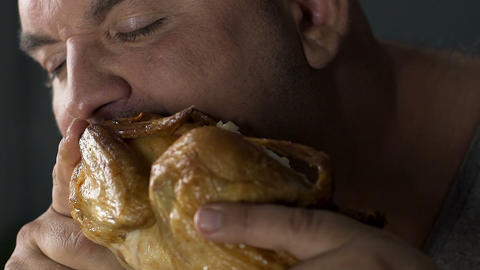 Plump male biting fried oily chicken, binge eating disorder, health problems Live Action