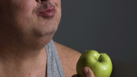 Fat male chewing green apple, dieting and calories counting, healthy lifestyle Live Action