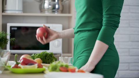 Slender woman coming to table taking apple and eating it, healthy nutrition Live Action