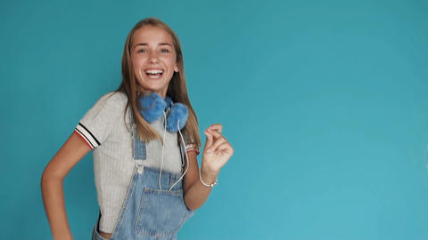 A little girl with big white teeth dancing on a blue background. Teen girl with Footage