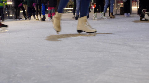 Unrecognizable skater's skim the ice on ice-rink in evening Footage