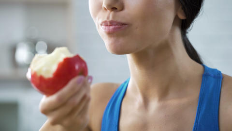 Girl eating apple replenishing her body with vitamins after grueling workout Footage