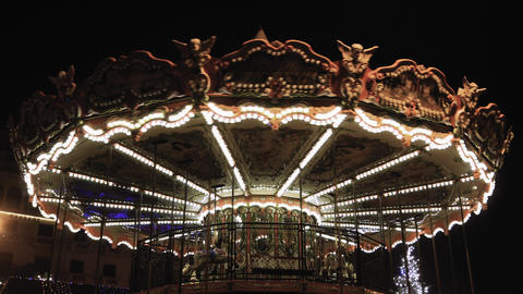 Illuminated vintage fairground carousel with wooden horses rotating at night GIF