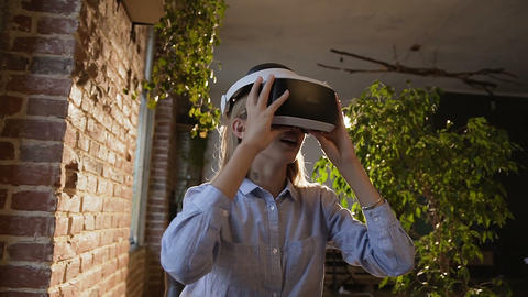 Beautiful young woman using 3D virtual reality headset. Virtual reality game Live Action