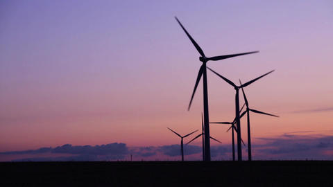 Close-up of silhouettes of wind turbines in the countryside under a beautiful Footage