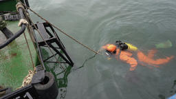 Professional diver in an orange diving suit swims to ships ladder GIF