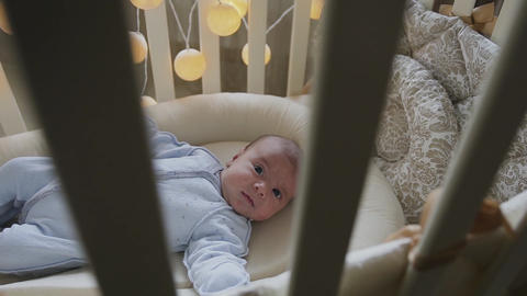 Newborn baby boy lying in the crib looks at camera. Cute little baby lying in Footage