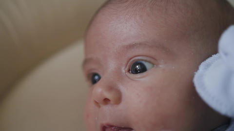 Portrait of a newborn baby lying on the crib in a bedroom. Close up, the face of Live Action