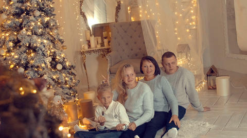 Joking family posing on New Year tree background in cozy home at holiday eve GIF
