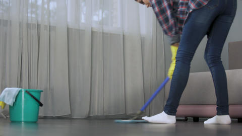 Housewife carefully washing floor in her apartment with mop, spring-cleaning Live Action