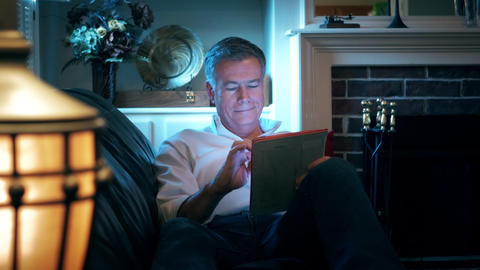 man reclining on his couch using an electronic tablet 4k Footage