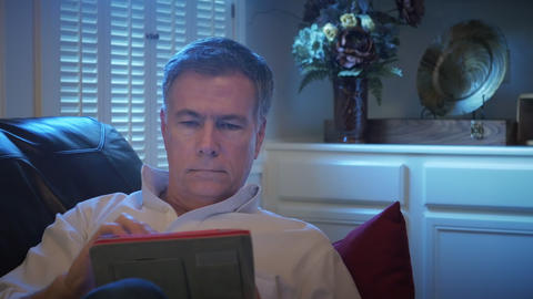 closeup man reclining on his couch using an electronic tablet 4k Footage