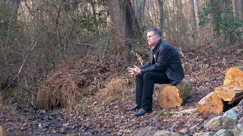 Man Sitting On A Log In The Forest Lost In His Thoughts stock footage