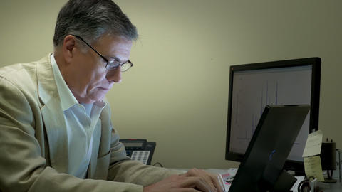 businessman working at his desk smiles at camera side view 4k Footage