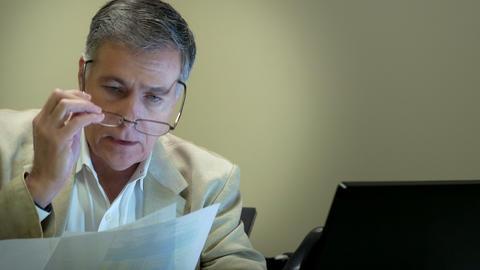 businessman working at his desk looking over paperwork 4k Footage