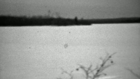 1937: Lone man venturing into winter cold snow skis without poles Footage