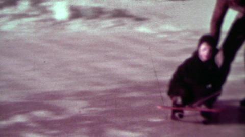 1937: Man ice skating pulling kid on winter snow sled around homemade rink Footage